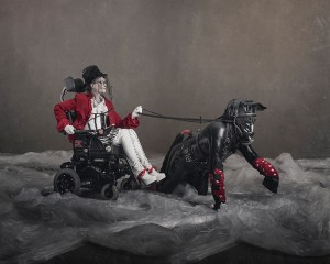 Person in electric wheelchair holding the reigns to a black leather clad human pony on all fours.