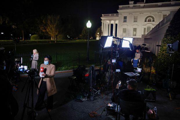 Des journalistes devant la Maison-Blanche, mardi soir.
