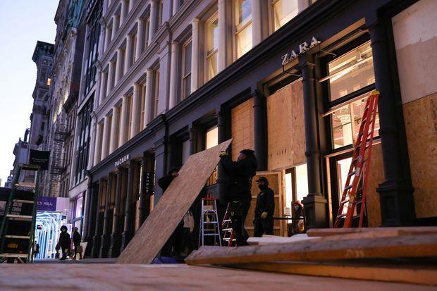 A New York, des salariés installent des protections devant un magasin, à la veille de l'élection présidentielle, lundi soir.