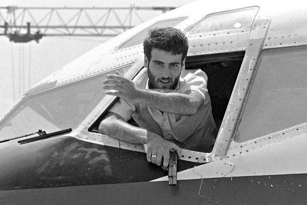 Un preneur d'otages lors de l'interview de John Testrake, organisée par les terroristes par la fenêtre du cockpit de l'avion, sur le tarmac de l'aéroport de Beyrouth, le 19 juin 1985.
