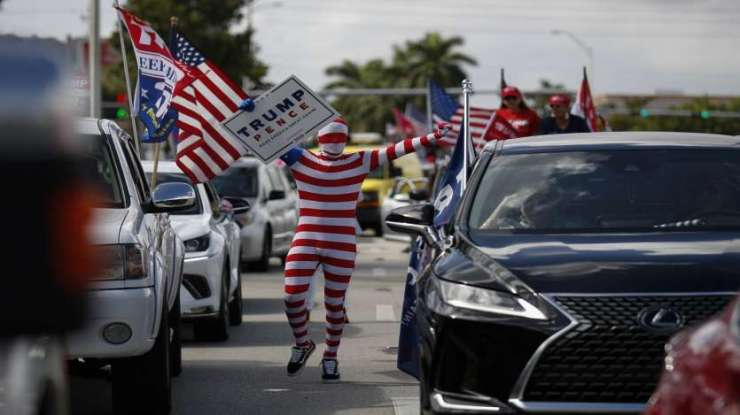 A man wearing a flag-themed body stocking walks between lines of cars as hundreds of vehicles gather for a car caravan in support of President Donald Trump, at Tropical Park in Miami.