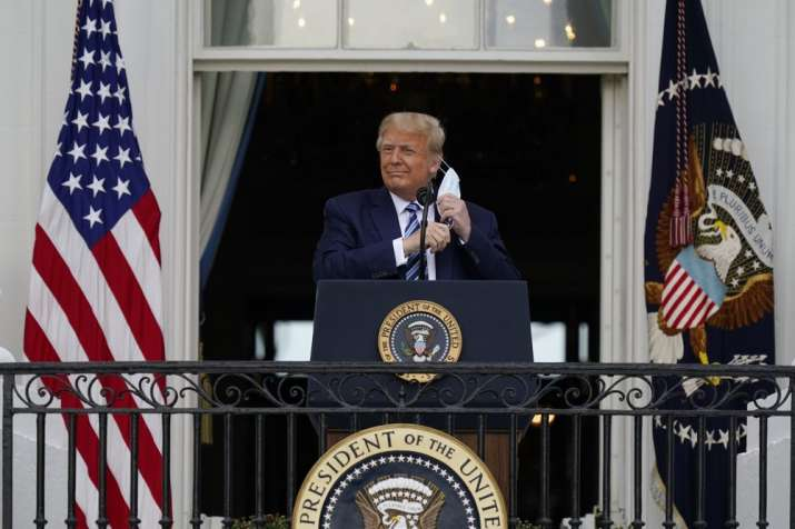 President Donald Trump removes his face mask to speak from
