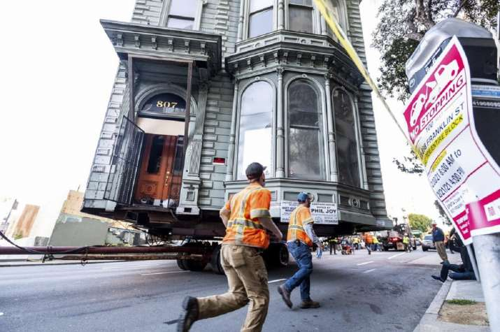 Workers pass a Victorian home as a truck pulls it through