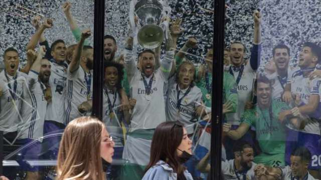 Two women walk past a Real Madrid poster of the team