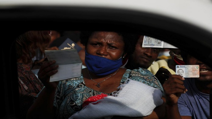 India Tv - Haitians wave their passports shouting