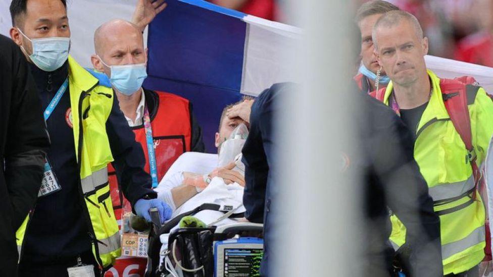 La imagen que tranquilizó al mundo: Christian Eriksen levanta la mano y asiente, luego de ser reanimado en plena cancha durante el partido entre Dinamarca y Finlandia por la Euro 2020.
