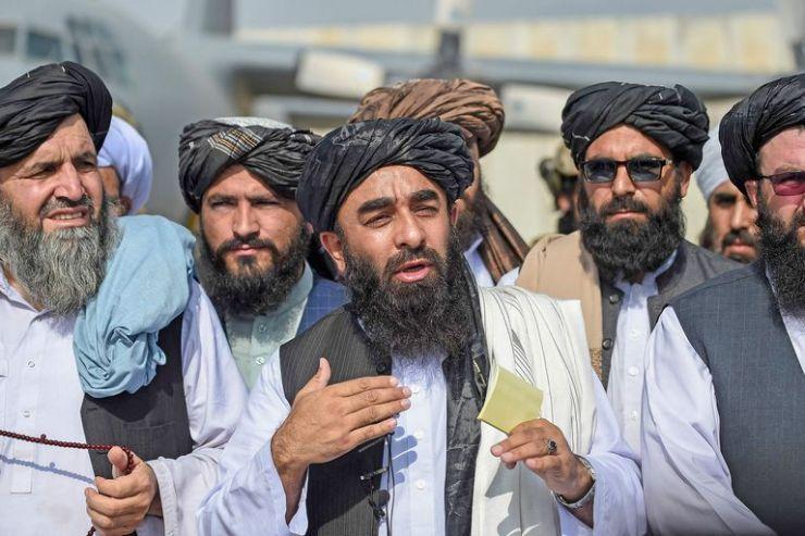 Mujahid (centro) habló con la prensa en el aeropuerto de Kabul