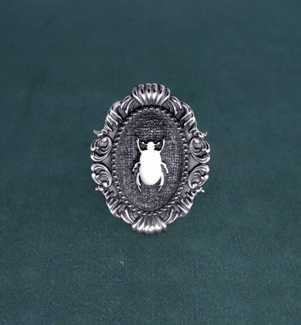 Bague scarabée noir sacré des égyptiens dans son cadre ovale mouluré, esprit baroque et musée en argent massif vue face | Res Mirum