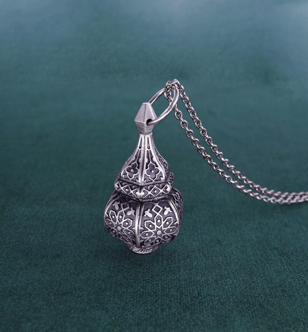 Pendentif mini lanterne en argent massif inspirée de l'artisanat maghrébin fabriqué en France vue posée | Res Mirum