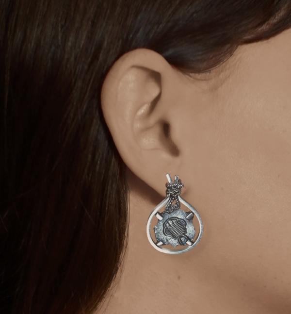 Boucles d'oreilles asymétriques avec motifs de fossiles de Limule & de Trilobite et de décors de fougères en argent fabriquée en France artisanalement portées trilobite | Res Mirum