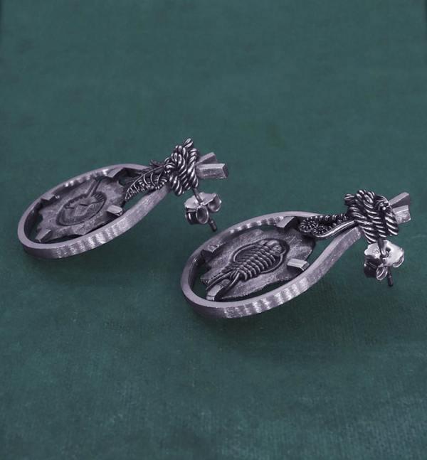Boucles d'oreilles asymétriques avec motifs de fossiles de Limule & de Trilobite et de décors de fougères en argent fabriquée en France artisanalement vue côté | Res Mirum