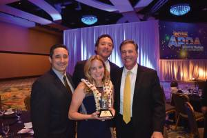 Jerilea Caldwell, executive assistant for Hilton Grand Vacations Club at the Flamingo and Hilton Grand Vacations Club on Paradise (center), with Alex Canales, Regional General Manager – Las Vegas, Hilton Grand Vacations (left); Mark Wang, President, Hilton Grand Vacations (top center); and Stan Soroka, Senior Vice President, Club, Resort and Brand Services, Hilton Grand Vacations (right).