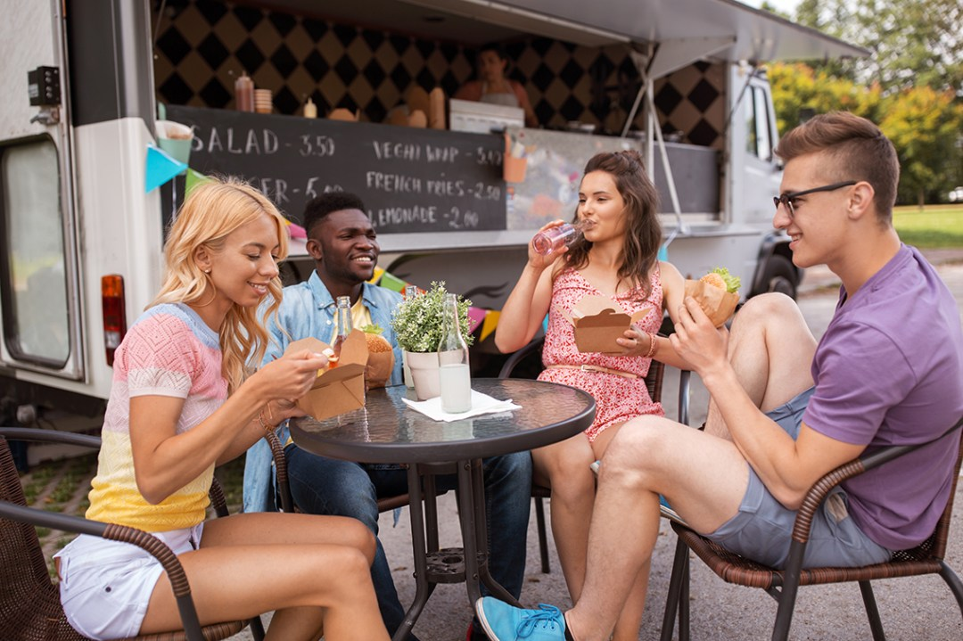 Friends dining outside of a food truck, a modern type of restaurant that's risen in popularity in recent years.