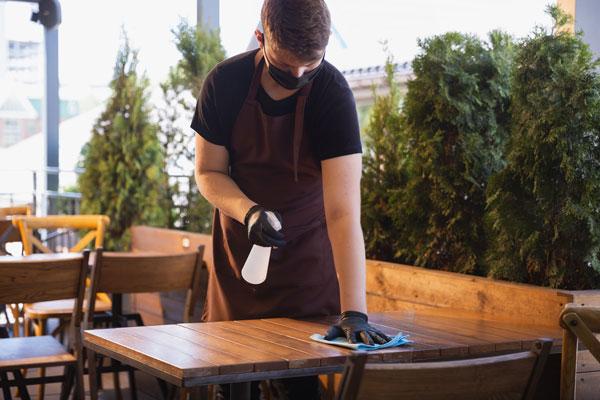 Server sanitizing restaurant table