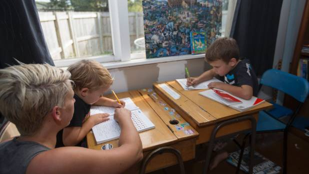 Hamilton woman Loral Morrison home schools her three kids. She's pictured in 'the library' with Jacob, 4, (left) and Zeke, 8.