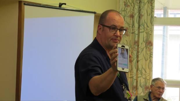 Charge nurse Nick Smith demonstrates the HealthTapp app.
