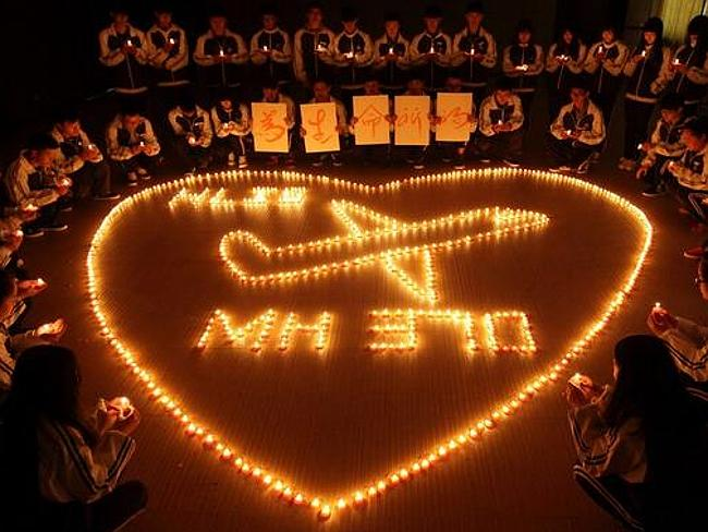 Prayer ... Students in East China pray for the passengers from the missing Malaysia Airli
