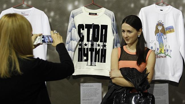 """Proactive ... A fashionista poses in front of T-shirts with the words """"Stop Putin"""" and """"G"""