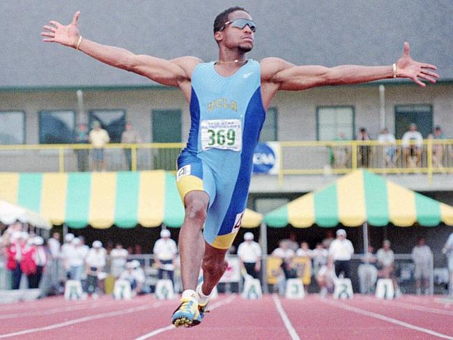 Ato Boldon raises his arms in victory as he wins the men's 100-meters at the NCAA Track a