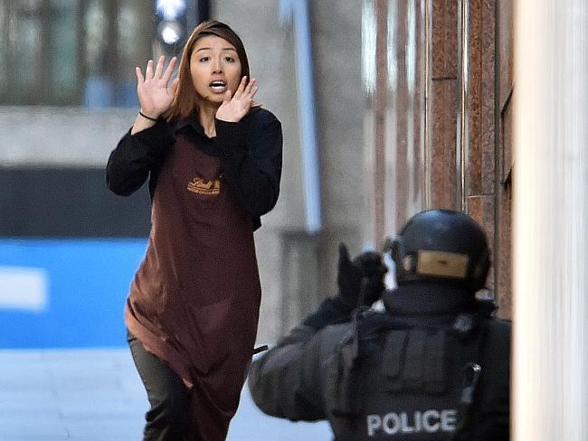 One of the hostages runs towards police from a cafe in the central business district of S