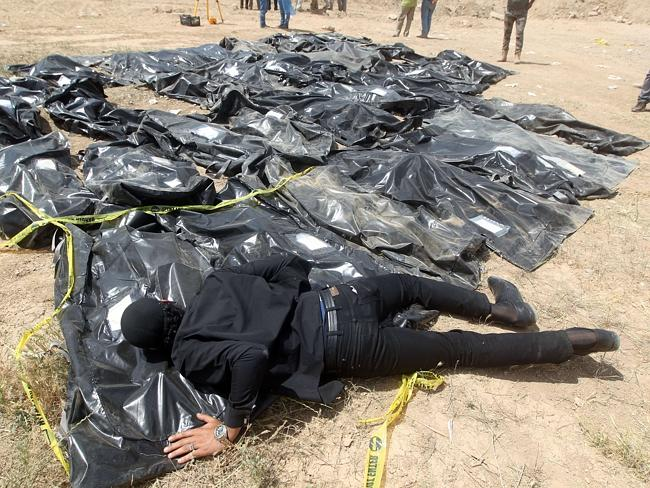Devastating discovery ... An Iraqi man cries over body-bags containing the remains of peo