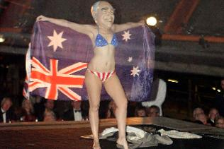 Gypsy Woods (in a John Howard mask) opens her wraparound Australian flag to reveal a Stars and Stripes bikini