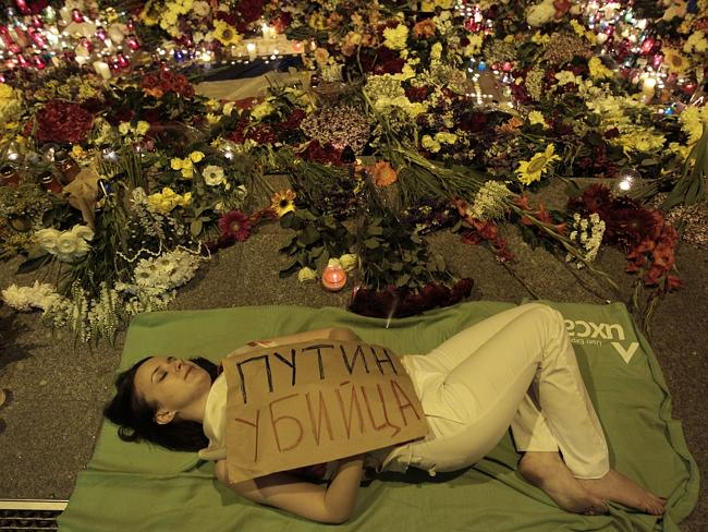 "Ukrainian woman lies down in front of Dutch embassy holding a poster reading ""Putin is a"