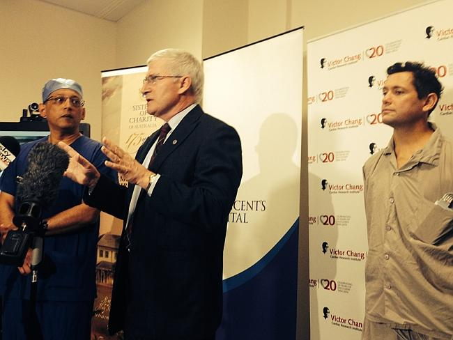 Doctors speak at the press conference while transplant patient Jan Damen looks on.