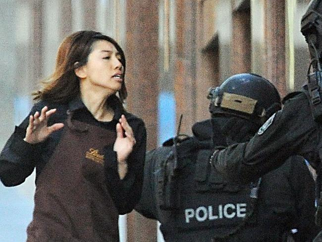 Unforgettable images ... a hostage runs from the Lindt Chocolate cafe in Martin Place, Sy