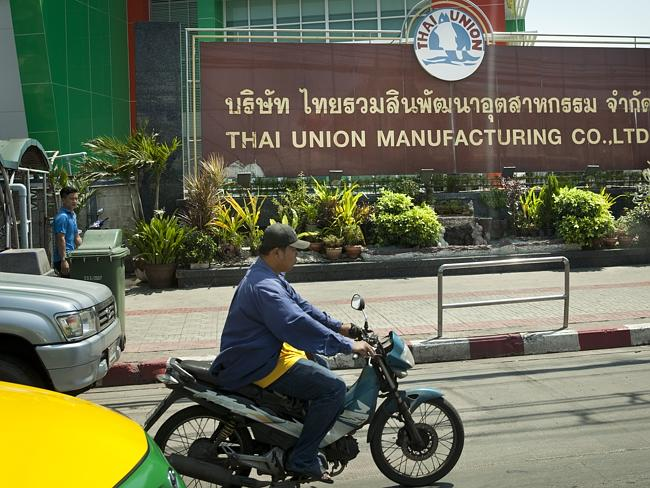A motorcyclist passes the Thai Union Manufacturing Company.