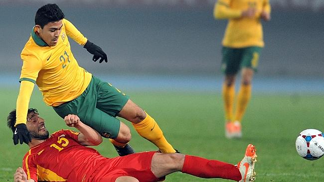 Macedonia's Dushko Trachevski (L) fights for the ball with Australia's Massimo Luongo.