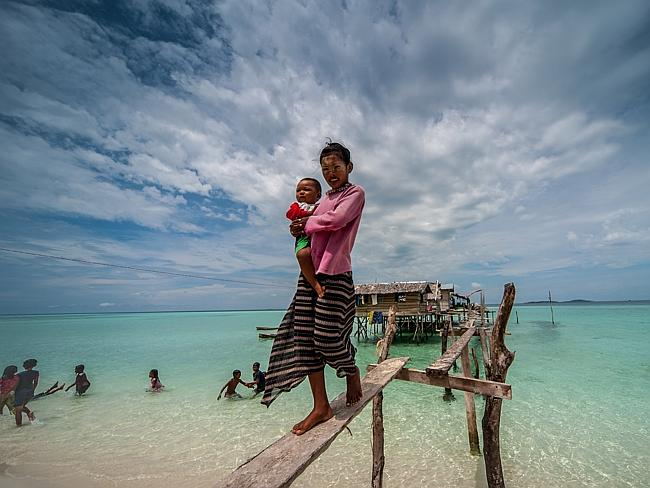 Along with their families, they live in wooden huts on stilts and trade their seafood for