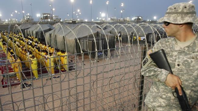 A soldier stands guard as detainees pray at a U.S. military detention facility Camp Bucca