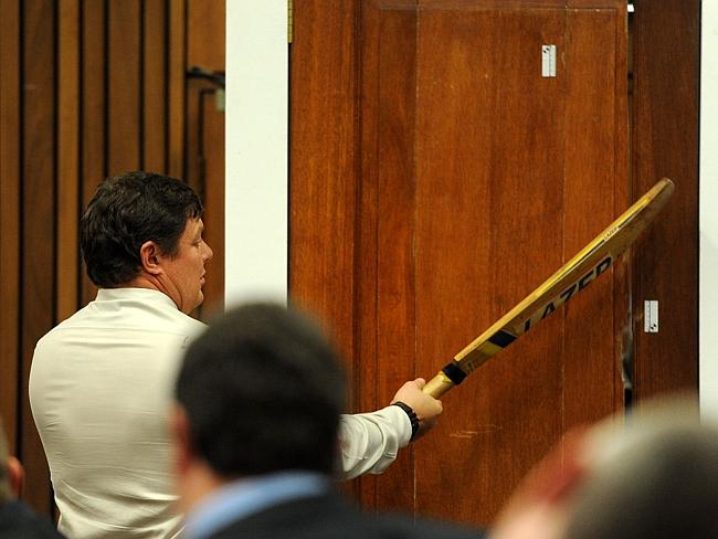 Match point ... Police forensic expert Colonel Johannes Vermeulen hits a door with a cric