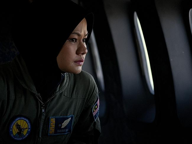 A crew member looks out the windows from a Malaysian air force CN235 aircraft during a se