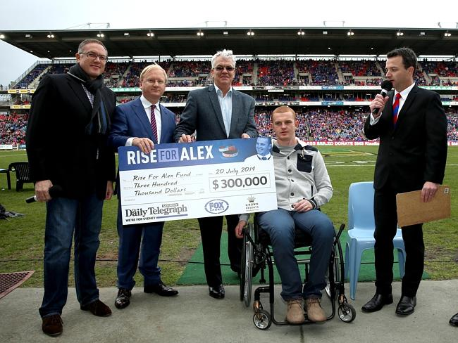 Daily Telegraph editor Paul Whittaker, second from left, presents a cheque to Alex McKinn
