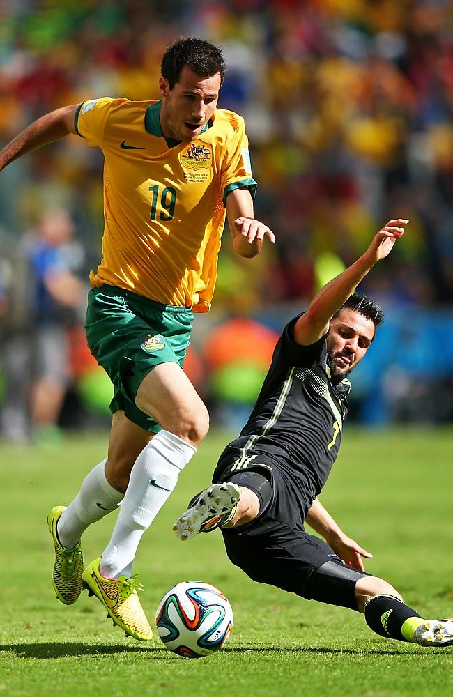 Ryan McGowan of Australia is challenged by David Villa.