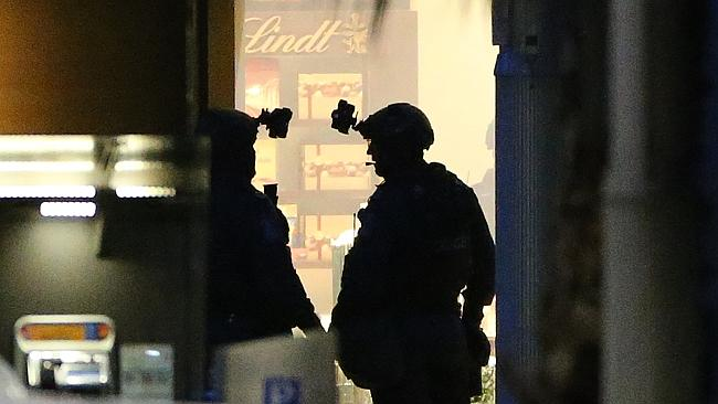 Two armed tactical response officers stand ready to enter the Lindt cafe.(AP Photo/Glenn
