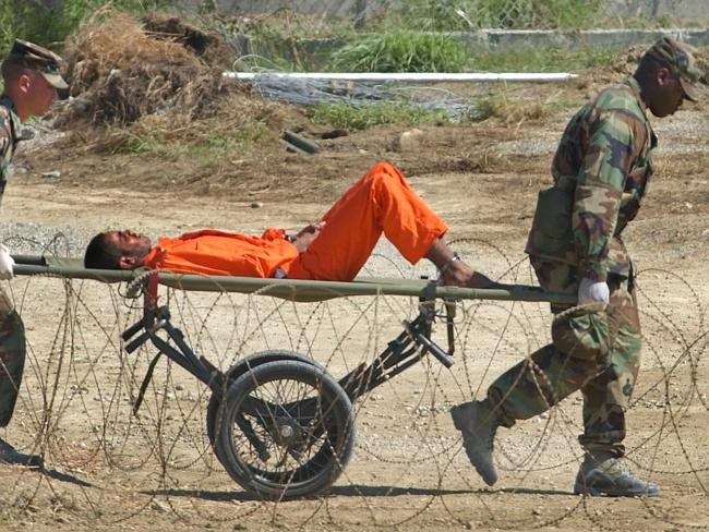 A detainee is carried on a stretcher before being interrogated.