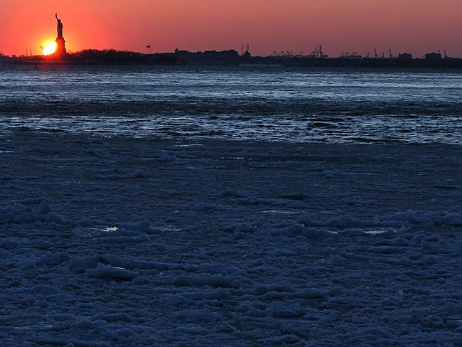 New York, New York ... Ice forms on the Brooklyn waterfront as the sun sets behind the St