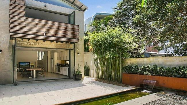 The rear garden features a tranquil water feature.