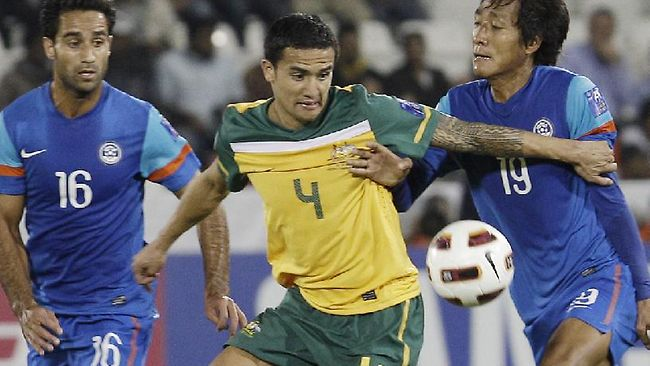 LET ME THROUGH: Socceroos striker Tim Cahill fends off the attention of