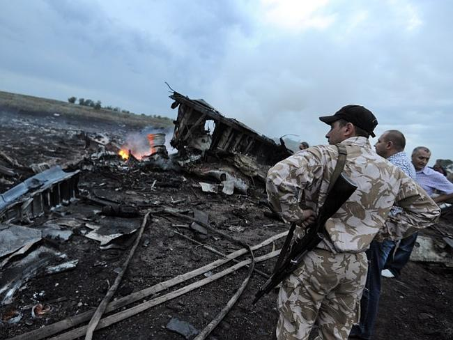 People stand next to the wreckage of the Malaysia Airlines flight. AFP PHOTO/DOMINIQUE FA