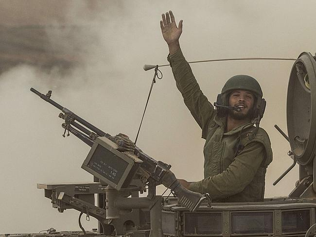 Battle rages ... An Israeli soldier waves to photographers from his armoured personnel ca