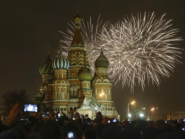 Fireworks explode over St Basil's Cathedral as people celebrate the New Year at the Red S