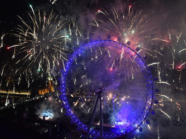 Fireworks explode around the Houses of Parliament and the London Eye during the New Year
