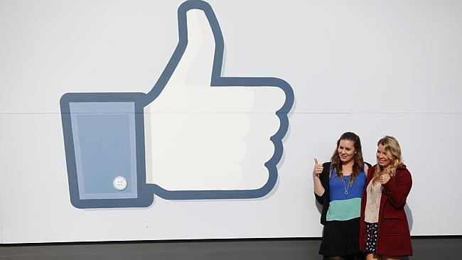 Visitors pose in front of Facebook's headquarters in Menlo Park, California.