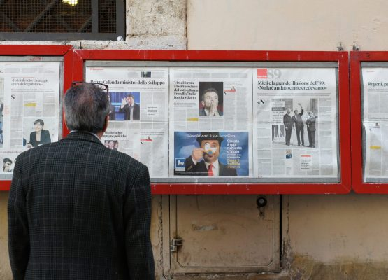 man reading newspaper in bulletin board