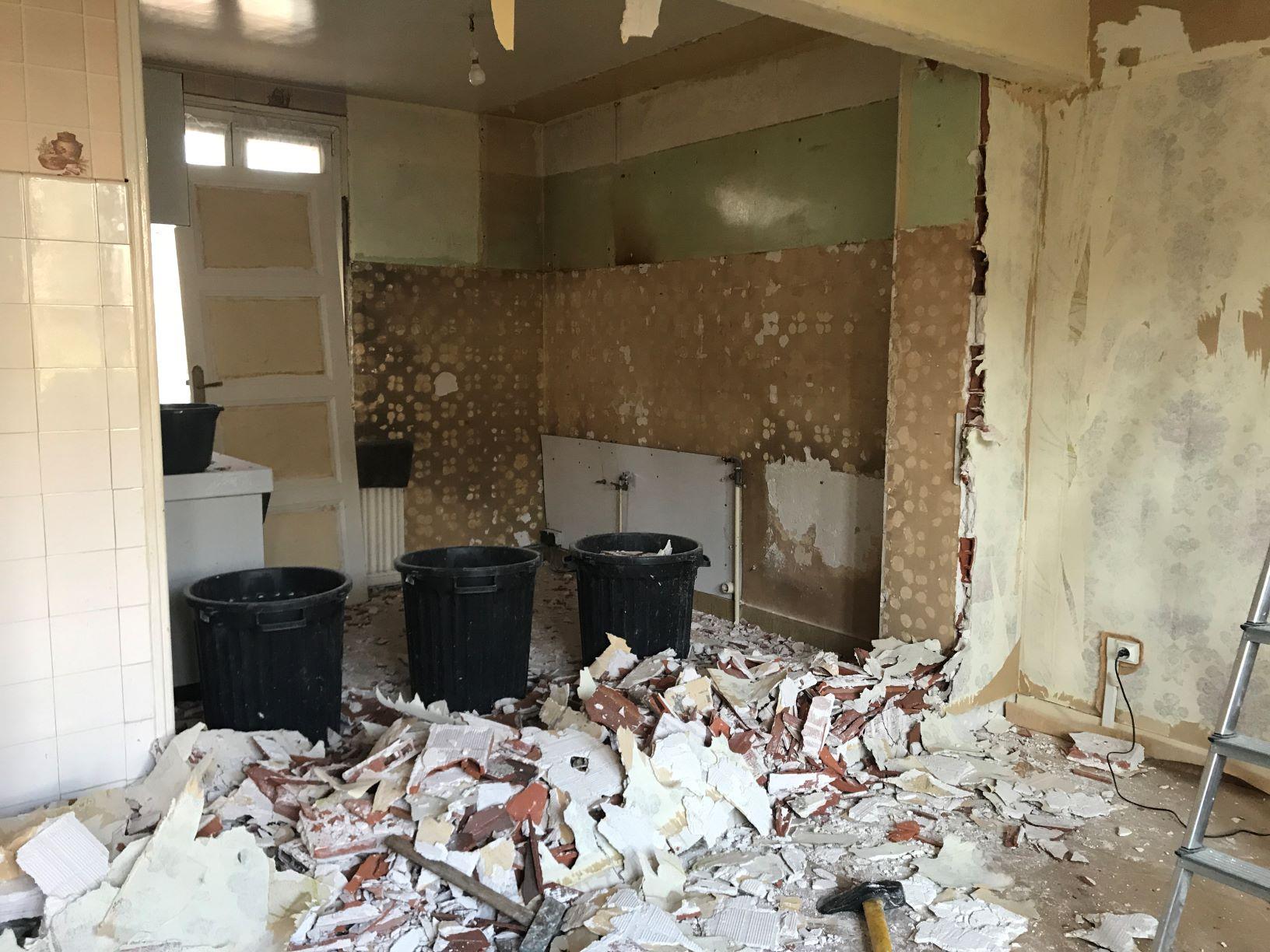 démolition d'une cloison en briques entre la cuisine et le salon dans un projet de rénovation de maison