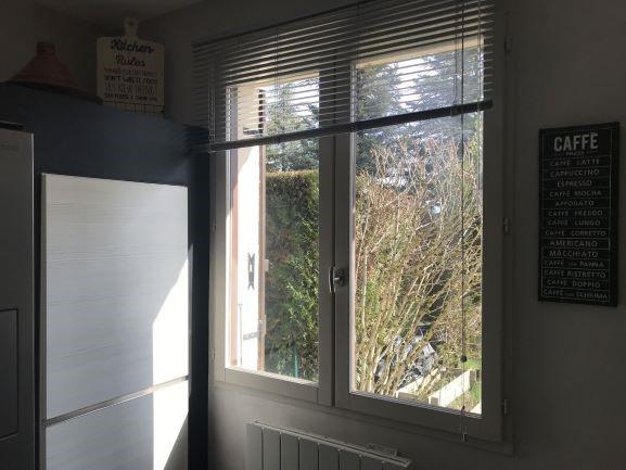 Dans ma cuisine, vue sur la fenêtre en bois qui a été modernisée grâce à un petit coup de peinture, coloris clair